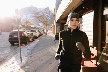 Focused teenage girl running along sunny winter sidewalk
