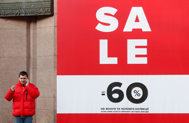 A man speaks on his mobile next to a sale sign outside of the Central Universal Department Store in Kiev