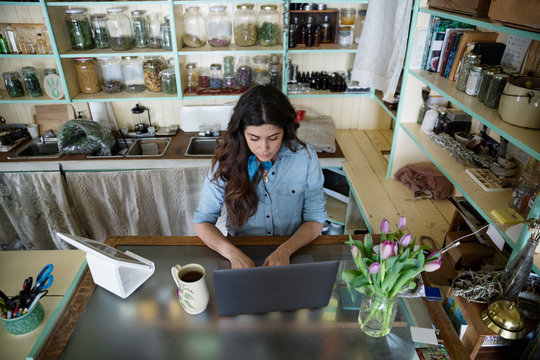 Female business owner working at laptop in apothecary shop