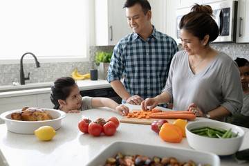 Family cooking, cutting vegetables in kitchen