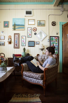 Woman reading book in living room