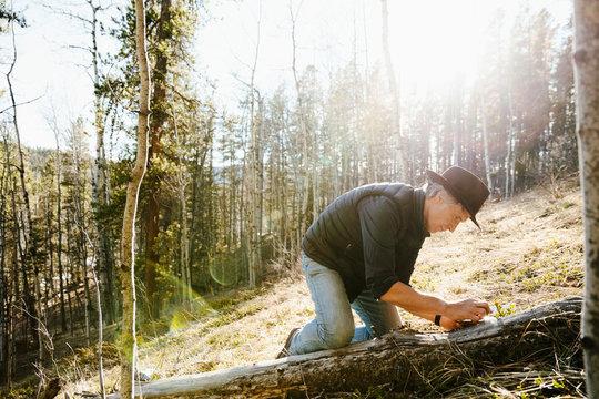 Man taking soil sample in sunny woods