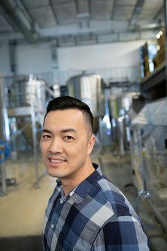 Portrait confident male brewer working in distillery
