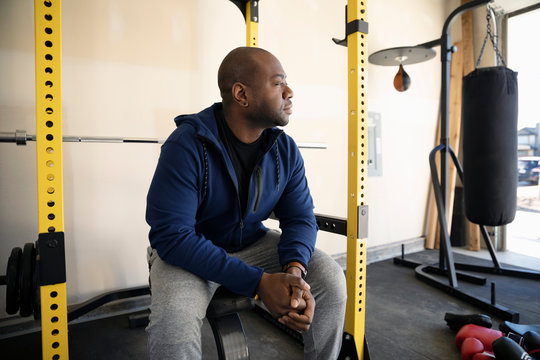 Thoughtful man lifting weights in garage