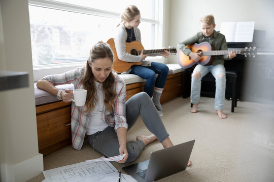 Mother working from home while children practice guitar in background
