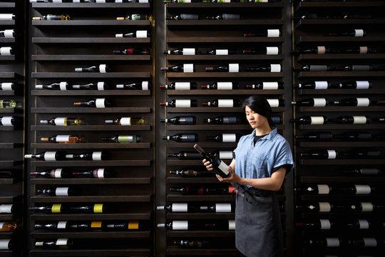 Female sommelier with wine bottle at wine rack in restaurant