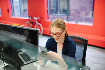 Businesswoman using smart phone at computer in office