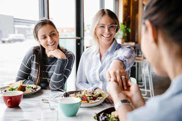 Happy young woman showing engagement ring to friends at lunch in cafe