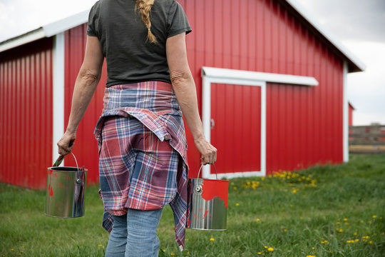 Female farmer with paint cans outside red barn