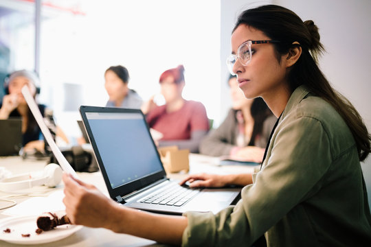 Focused female computer programmer coding at laptop in office