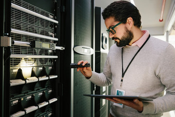 Male IT technician with flashlight and digital tablet examining equipment in network server room Wall mural