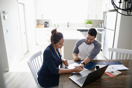 Couple paying bills, planning at laptop
