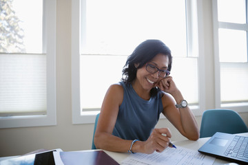 Smiling mature female student studying at laptop
