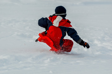 active boy falling from a sled