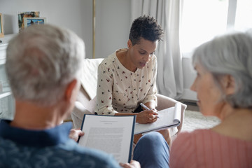 Financial advisor meeting with senior couple in living room