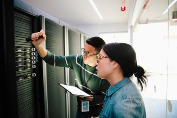 IT technicians with flashlight talking in network server room Wall mural