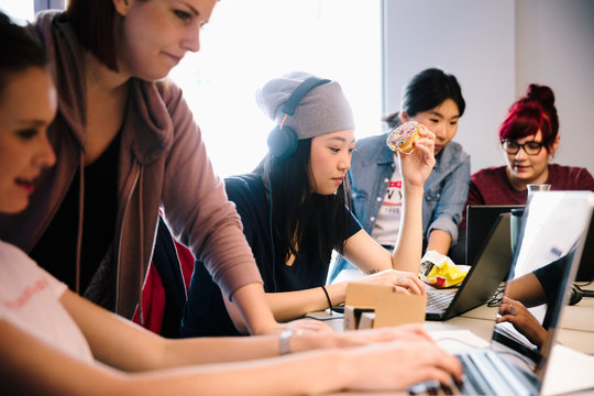 Female computer programmers coding in office