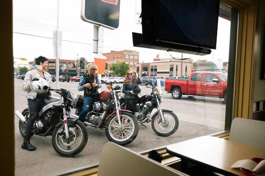 Women friends on motorcycles in parking lot outside drive-in