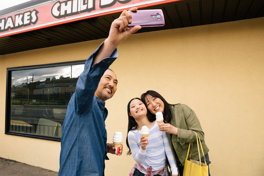 Family with camera phone taking selfie and eating ice cream outside drive-in
