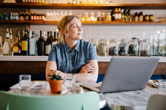 Female cafe owner working at laptop in cafe