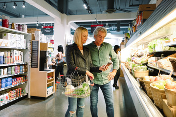 Senior couple with smart phone shopping for produce in grocery store