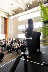 Businesswoman with microphone and digital tablet leading conference presentation