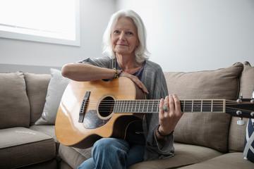 Portrait smiling senior woman playing guitar on living room sofa