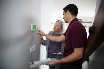 Service technician helping senior woman with digital thermostat