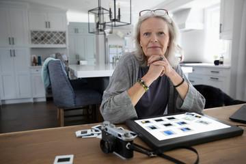 Portrait confident senior woman looking at photograph slides lightbox Fotoväggar