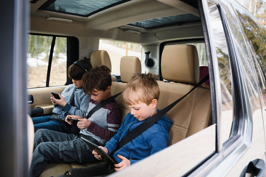 Brothers using smart phones and digital tablet in back seat of SUV