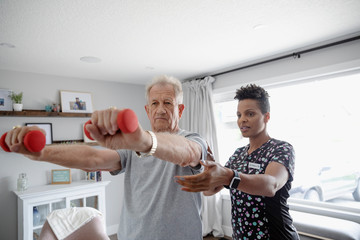 Home healthcare nurse helping senior man exercise with dumbbells