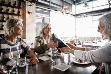 Senior women friends enjoying birthday lunch in restaurant