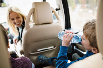 Mother watching thirsty son drinking from water bottle in back seat of SUV Fototapete