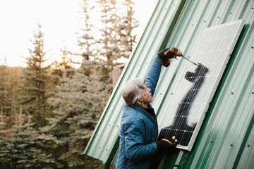Man installing solar panel on cabin roof