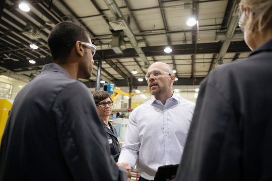 Male supervisor shaking hands with machinists in factory