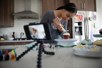 Teenage girl vlogging, decorating cupcakes in kitchen