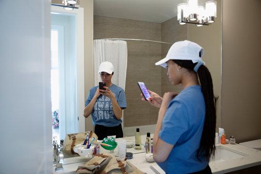 Teenage girl in work uniform using smart phone in bathroom mirror