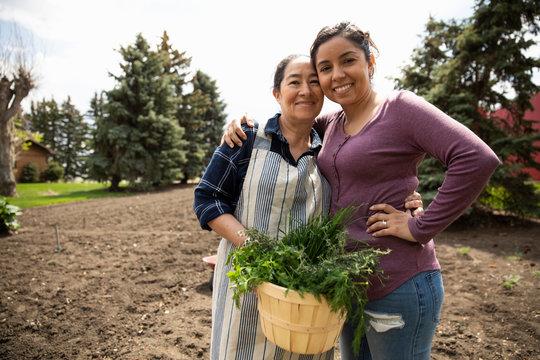 Portrait mother and daughter gardening, harvesting vegetables in sunny garden