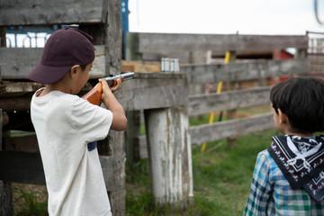 Boys with pellet gun on farm
