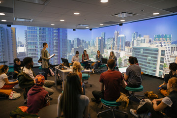 Students in VR classroom with projections of city scene