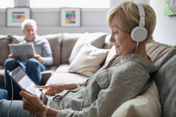 Senior woman with headphones and digital tablet listening to music on living room sofa