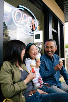 Happy parents and daughter with down syndrome eating ice cream outside drive-in