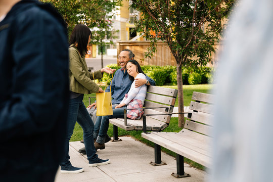 Happy parents and daughter with down syndrome with shopping bag on park bench