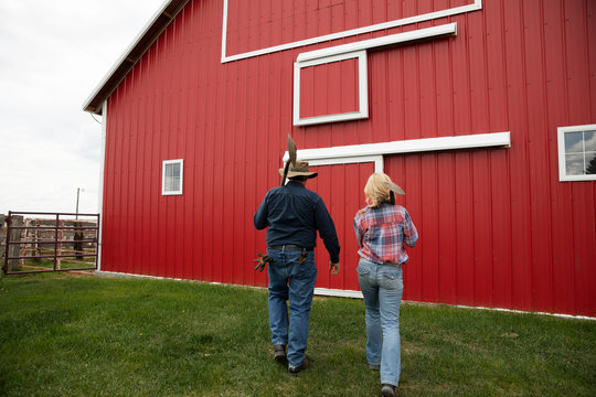Farmer couple walking toward red barn on farm