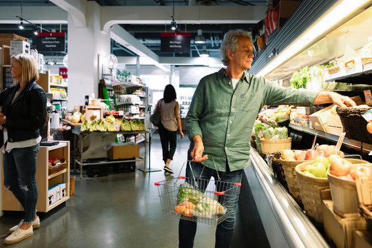 Senior man shopping for produce in grocery store