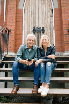 Portrait confident senior couple with smart phone on front stoop