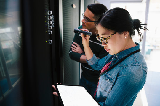 IT technicians with flashlight and digital tablet talking in network server room