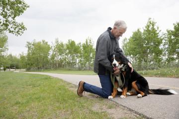 Senior man with dog in park Fotobehang