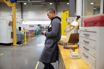 Male machinist using smart phone in factory