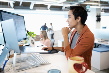 Focused businesswoman working at computer in open plan office